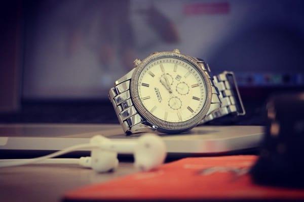 reloj plateado de hombre encima de una mesa